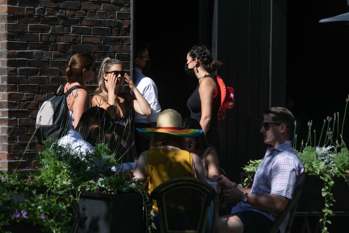 Nine Millennials are seen enjoying a day out at a venue on Chicago's Gold Coast Saturday — only two are wearing masks.