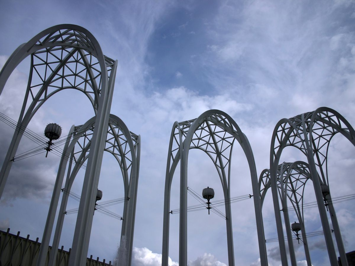 Five arches with latticed tops and four-leg bases set against a mostly-cloudy sky.