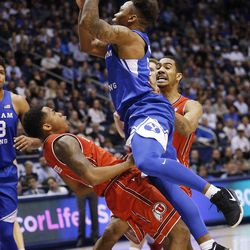 Brigham Young Cougars guard Jahshire Hardnett (0) is called for charging on Utah Utes guard Justin Bibbins (1) in Provo on Saturday, Dec. 16, 2017. BYU won 77-65.