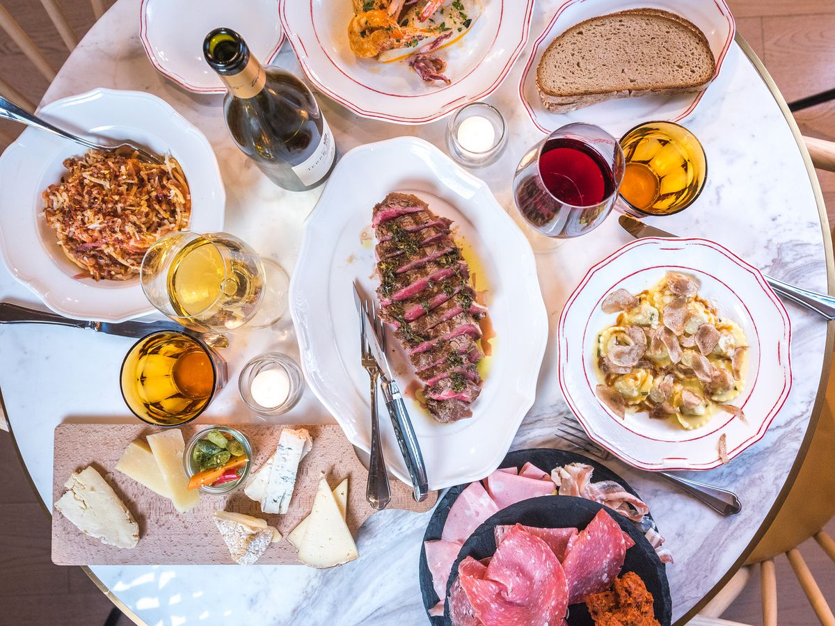 An overhead shot of table full of plates containing sliced steak, pasta, and a salumi tower.