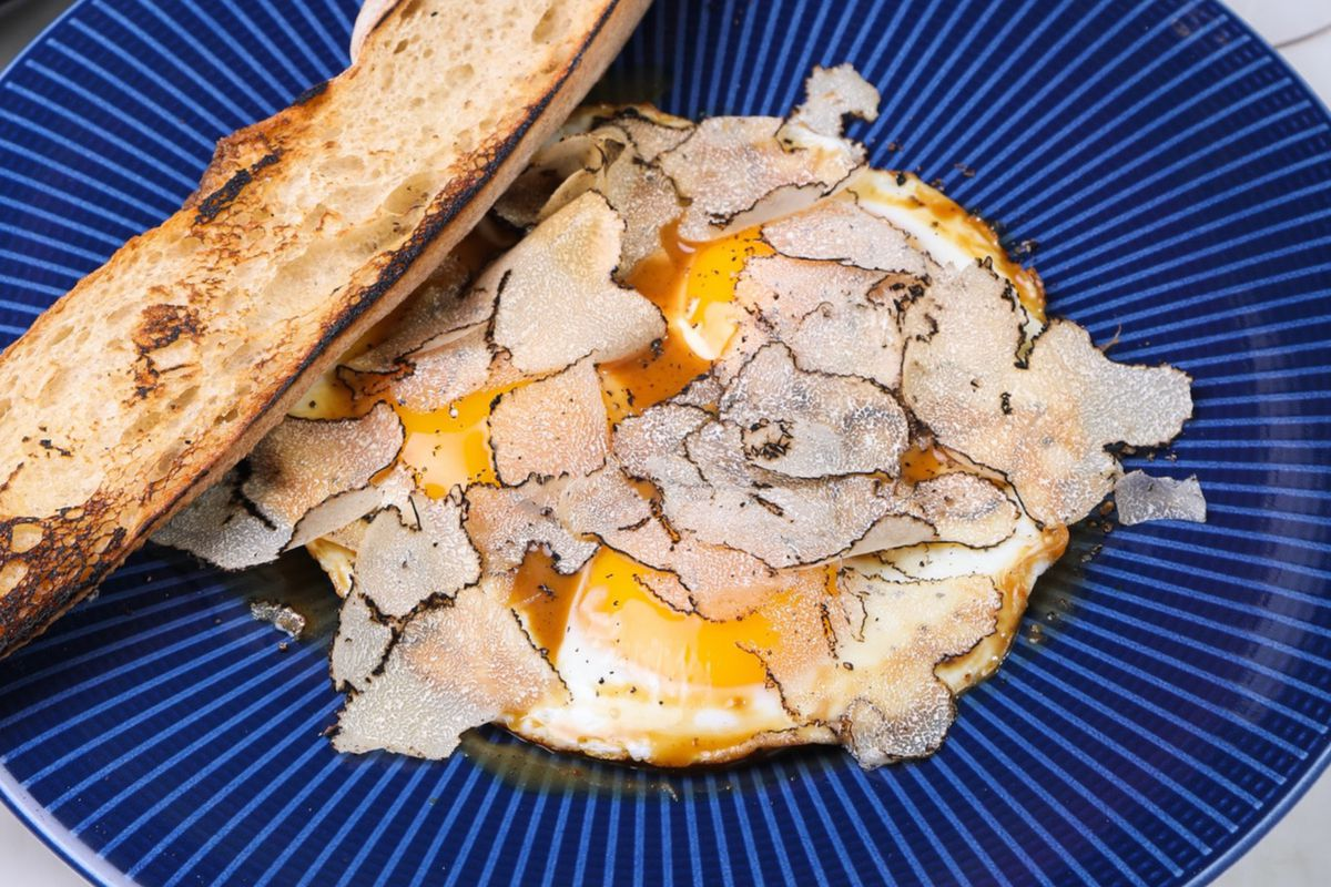 A blue plate with eggs and a side of bread