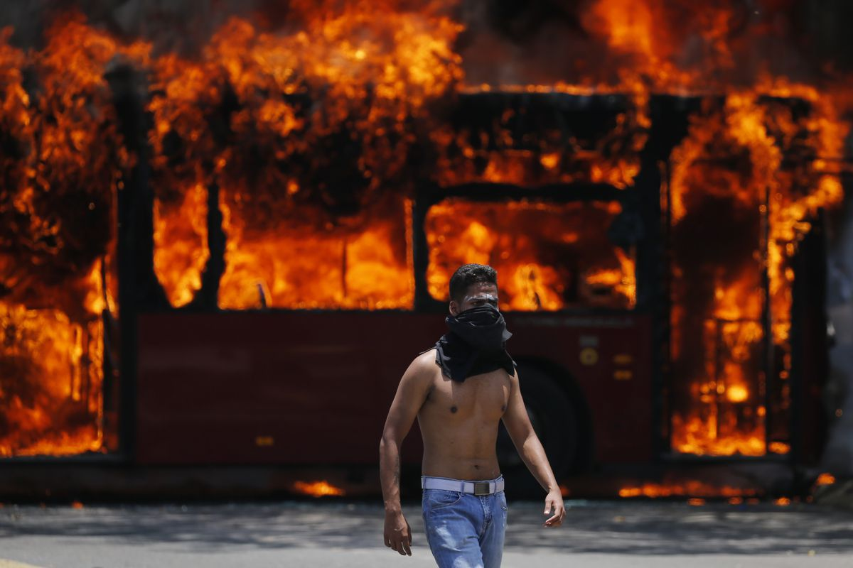 An anti-government protester walks near a bus that was set on fire by opponents of Venezuela's President Nicolas Maduro during clashes between rebel and loyalist soldiers in Caracas, Venezuela, Tuesday, April 30, 2019. Venezuelan opposition leader Juan Gu