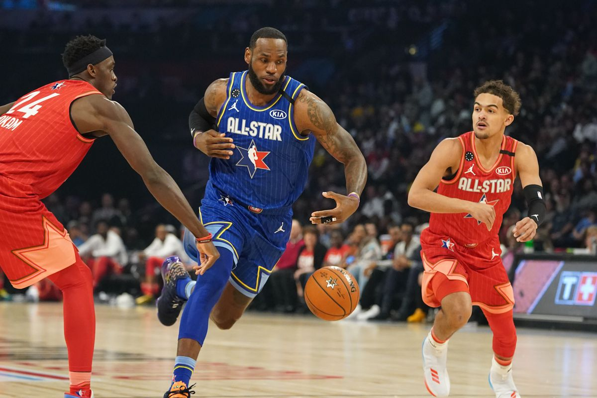 Team LeBron forward LeBron James of the Los Angeles Lakers drives between Team Giannis forward Pascal Siakam of the Toronto Raptors and Team Giannis guard Trae Young of the Atlanta Hawks during the 2020 NBA All Star Game at United Center.