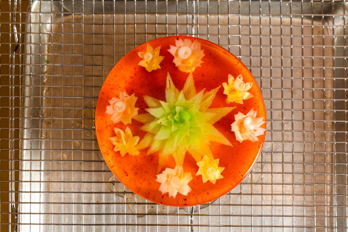 A red and green floral jelly cake is heated up in a pot and then placed over a wire rack.