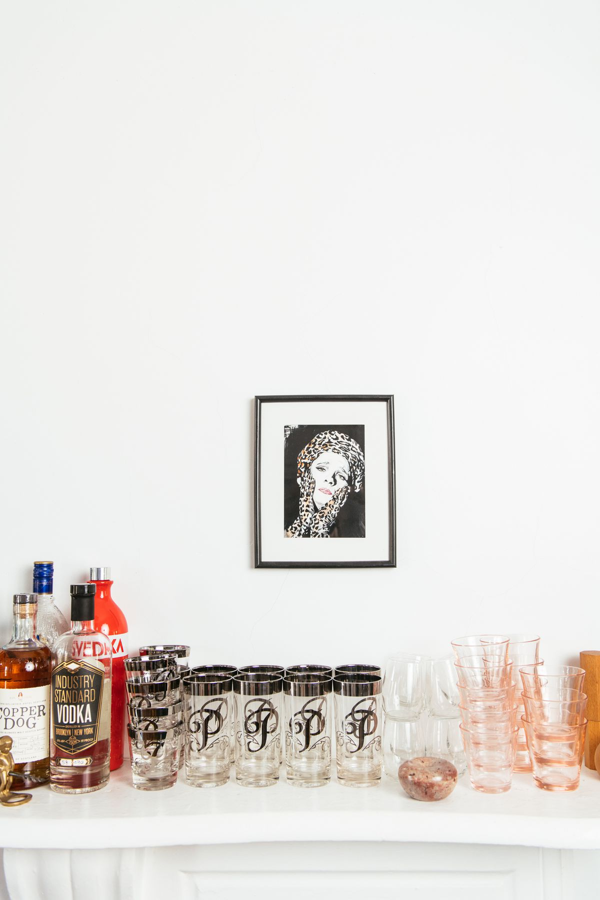 A white bar cart with bottles of liquor, and an assortment of glasses. A framed work of art which is a portrait of a woman in black and white hangs above the bar cart.