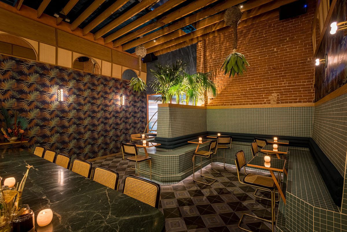 Tile seating and hanging plants at a moody cocktail bar.