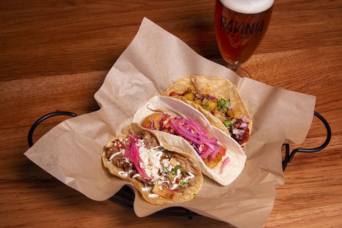 A basket with parchment paper and three tacos, with a glass of ale in the background.