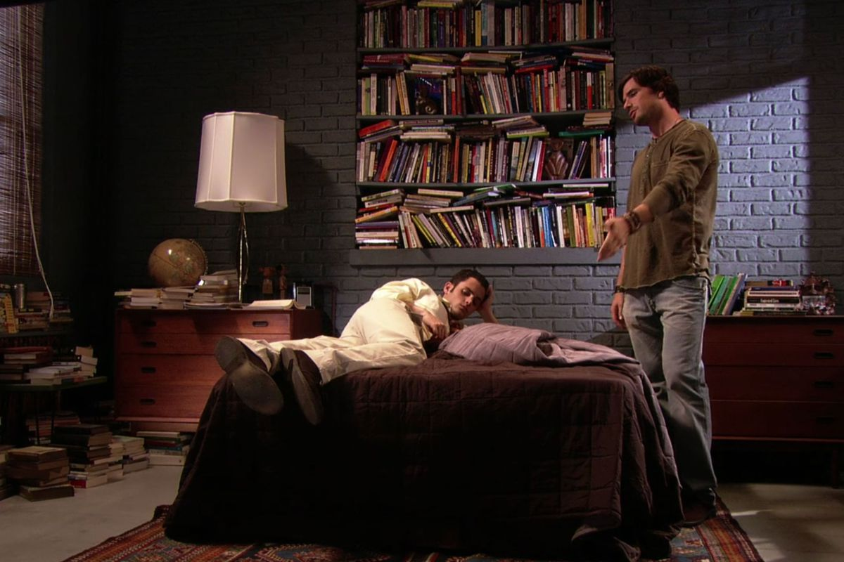 A bedroom. There is an exposed brick wall which is painted grey. On the wall are shelves with many books haphazardly stacked. There is a bed, bedside table, dresser, and lamp. There is a man standing next to the bed gesturing.