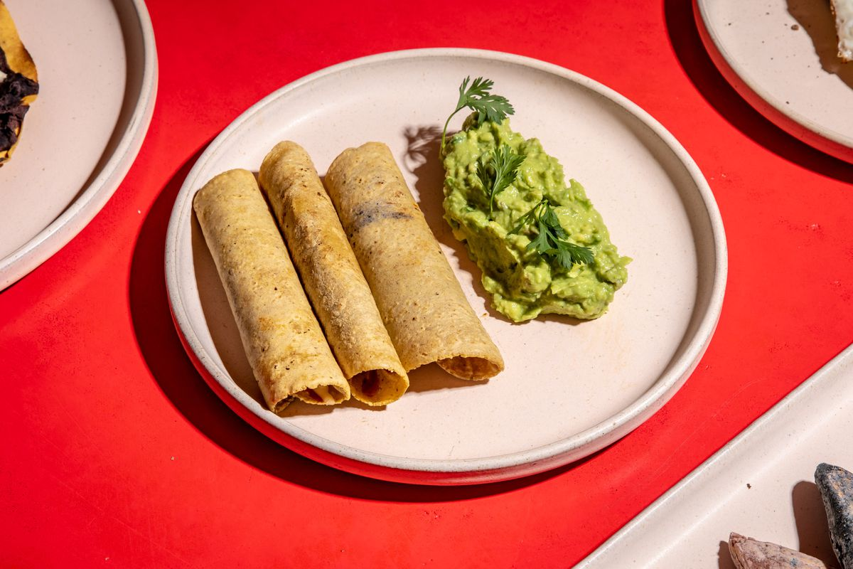 Flautas sit on a white plate next to guacamole over a red bar top