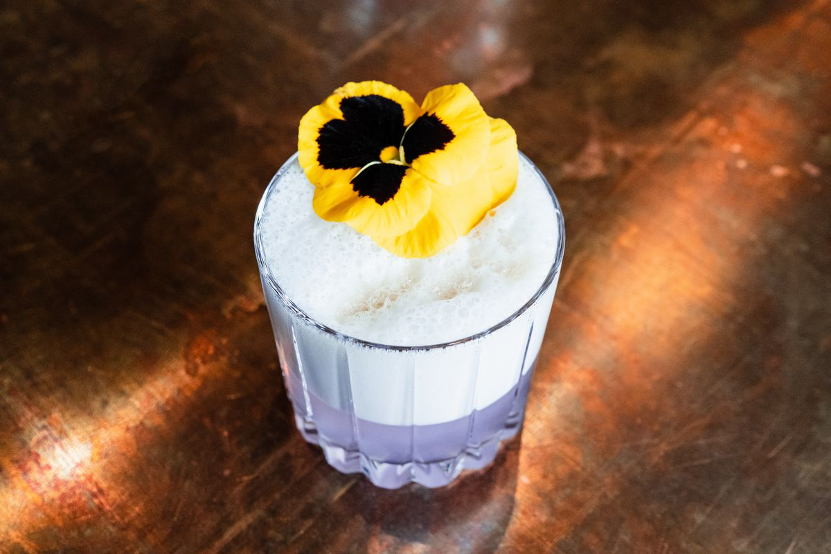 A drink with a frothy top is garnished with a yellow pansy. The liquid inside is a pale violet color.