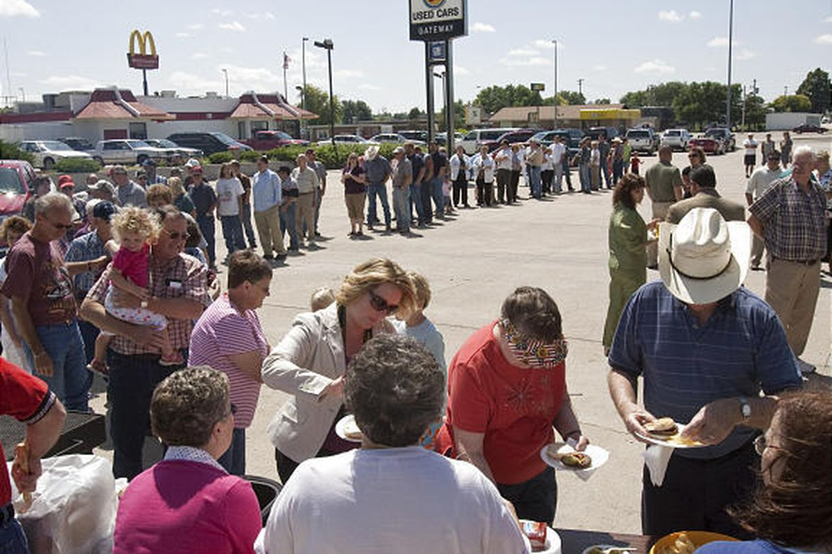 People enjoy a barbecue Thursday at Gateway Motors, a recently reinstated GM dealership in Broken Bow, Neb.