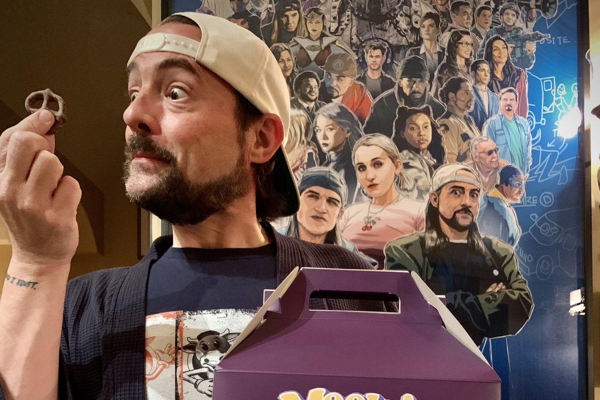 Actor and writer Kevin Smith holds a salted chocolate pretzel.