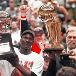 Michael Jordan holds the '98 Finals MVP trophy and coach Phil Jackson holds the NBA championship trophy.