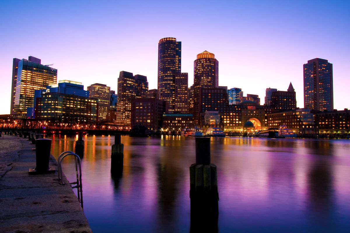 A view of Boston's skyline, featuring skyscrapers over the water, at dusk. The sky and water are shades of deep blue and purple.