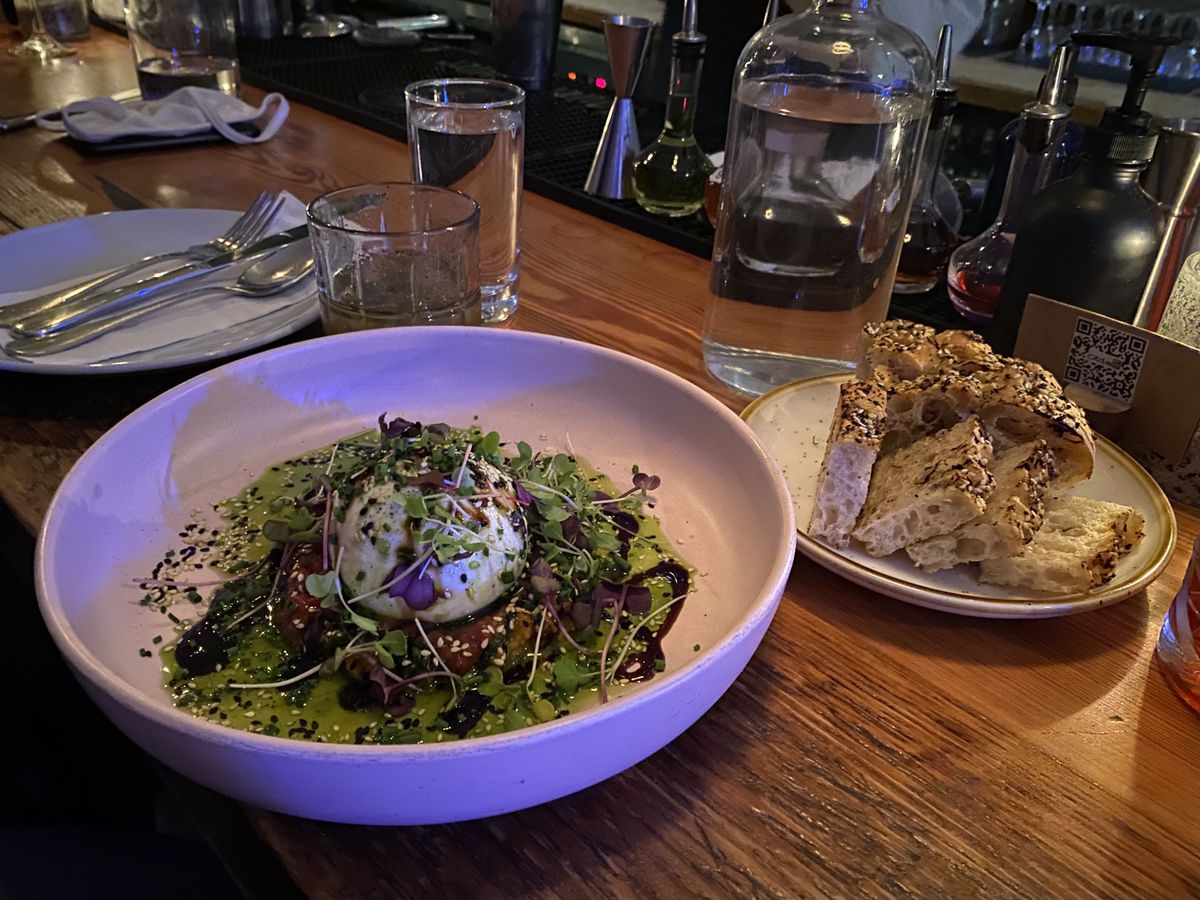 A bowl of burrata surrounded by pesto and topped with seeds and greens pools in a high-walled bowl beside a plate of focaccia.