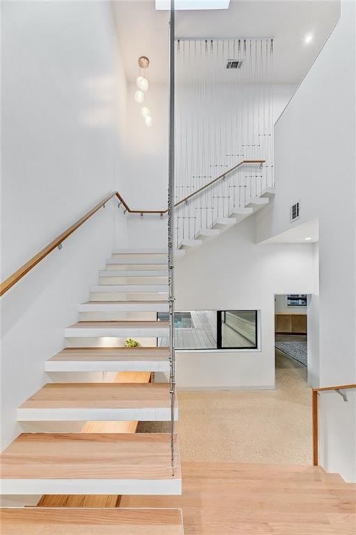 A stairwell landing with four wooden stairs below it that continues up the wall and around a corner to a second story open at the top of a two-story wall.