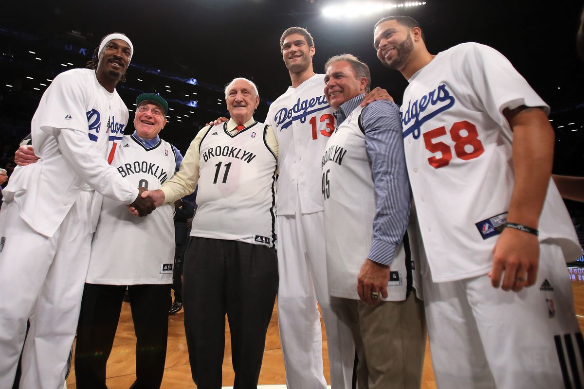 Former Brooklyn Dodgers Ralph Branca, Joe Pignatano and Gil Hodges's son Gil Hodges Jr. exchange jersey with Gerald Wallace (45),Brook Lopez (11) and Deron Williams (8). (Photo by Elsa/Getty Images)