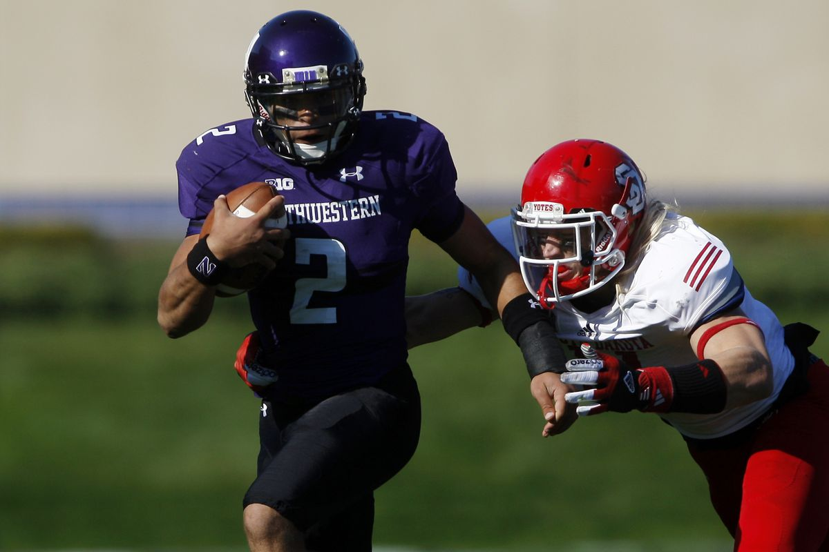 Sep 22, 2012; Evanston, IL, USA; Northwestern Wildcats quarterback Kain Colter (2) is tackled by South Dakota Coyotes linebacker Tyler Starr (11) during the second quarter at Ryan Field.  Mandatory Credit: Jerry Lai-US PRESSWIRE
