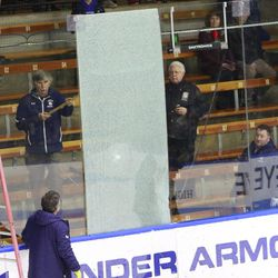 Yale's ice crew gets ready to repair a pane of glass broken during UConn's warmups before their game.