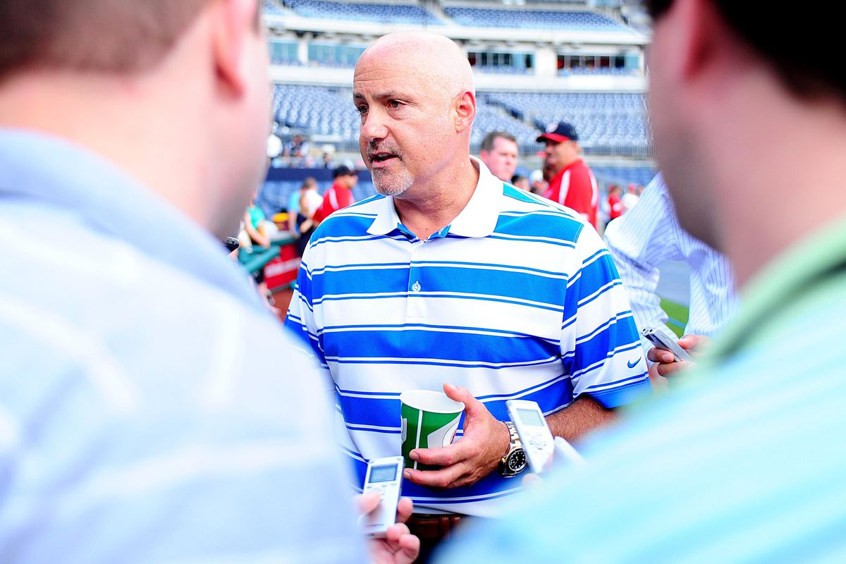 July 31, 2012; Washington D. C., USA; Washington Nationals general manager Mike Rizzo (center) talks to reporters prior to the game against the Philadelphia Phillies at Nationals Park. Mandatory Credit: Evan Habeeb-US PRESSWIRE