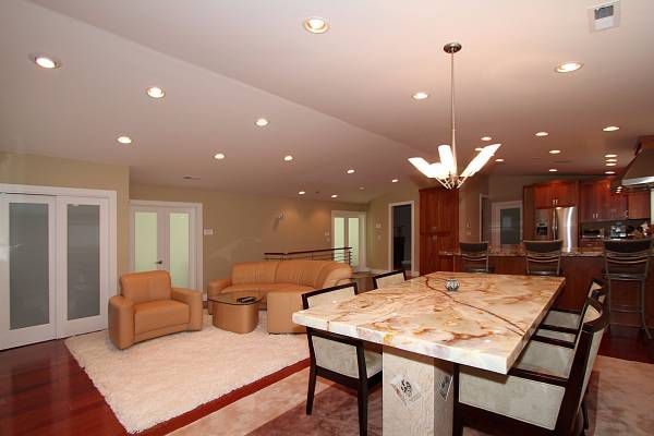 A marble-top dining room table with leather sectional and kitchen in the background