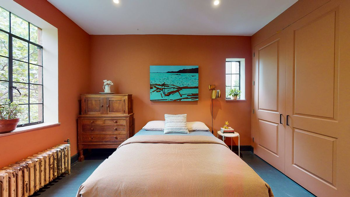 A bedroom with dark orange walls, a bed, and a large casement window.