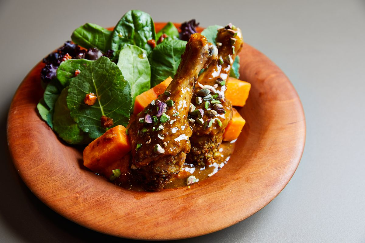 A shallow wooden bowl filled with two pistachio-crusted drumsticks, cubes of orange squash, and leaves of dark green lettuce
