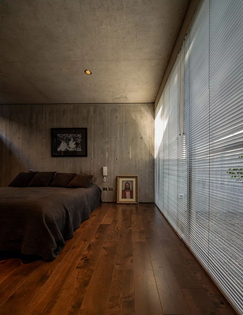 A bedroom in basement with wood floors, concrete ceiling and wall, and a facade of glass walls covered with blinds. A bed with gray bedding sits i the center.