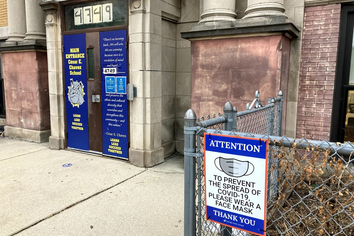 Signs posted outside a Chicago elementary school ask all who enter to wear a face mask.