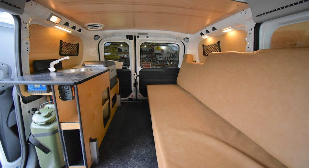 The interior of a camper can. There are seats and a sink.