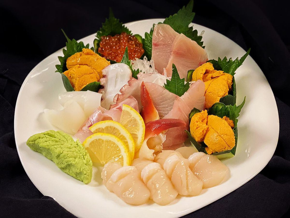 Platter of sushi including scallops, uni, and various items of sashimi with garnishes