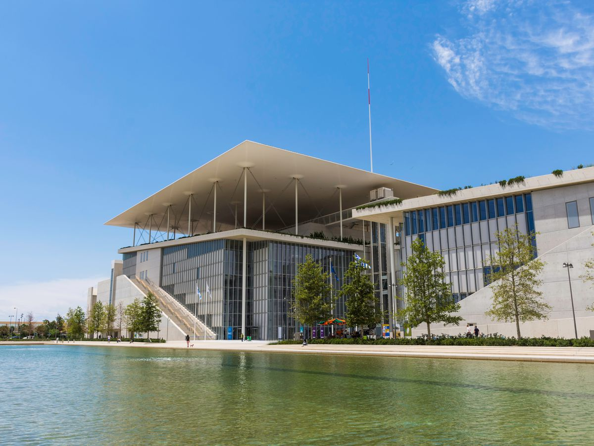 The exterior of the Stavros Niarchos Foundation Cultural Center in Athens. The facade has a thin concrete roof and mixed use of glass, steel, wood, and marble.