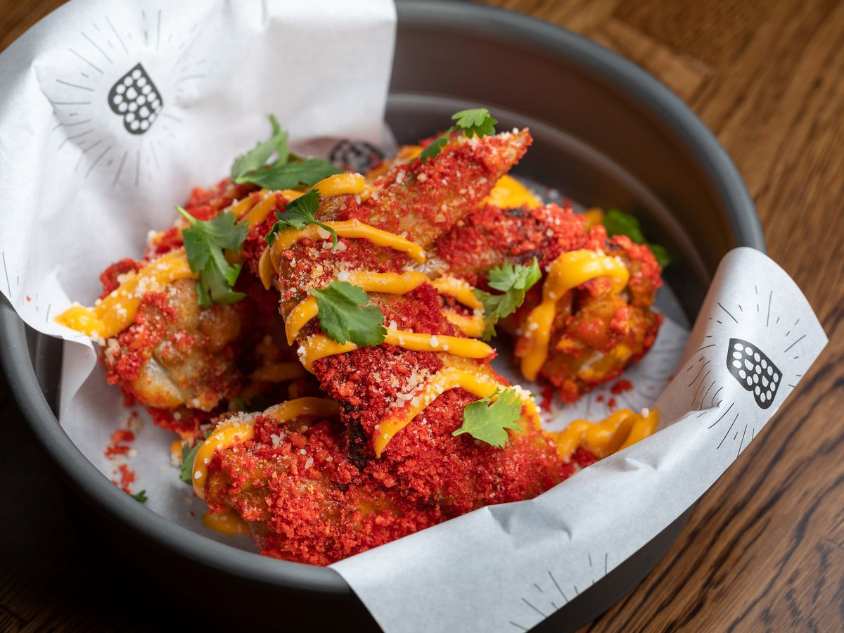 A basket of flamin' hot crusted cheetos wings with nacho drizzle.
