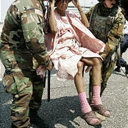 Army chaplain Thomas Holmes, left, and Spc. Jeffrey Madden of the 4th Infantry Division from Fort Hood, Texas, rescue an unidentified victim of Hurricane Katrina in New Orleans.