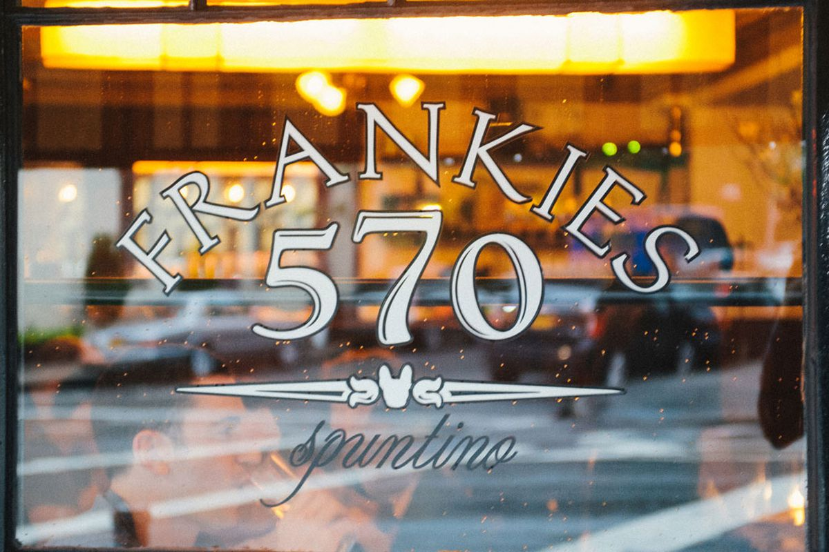 A restaurant window that reads Frankies 570 Spuntino