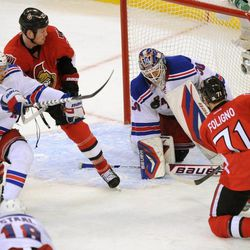 Ottawa Senators' Nick Foligno attempts to get the puck past New York Rangers' Henrik Lundqvist, as Senators' Chris Neil, second from left, holds off Rangers' Michael Del Zotto during the third period of Game 6 of a first-round NHL Stanley Cup playoff hockey series, in Ottawa, Ontario, on Monday, April 23, 2012.