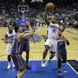 Orlando Magic's Jameer Nelson, second from right, drives to the basket for a shot between Charlotte Bobcats' D.J. Augustin, right, and Byron Mullens, front left, during the first half of an NBA basketball game, Wednesday, April 25, 2012, in Orlando, Fla.