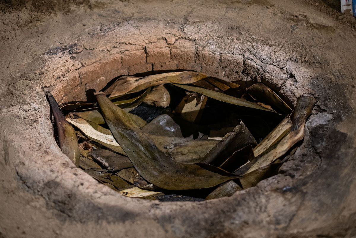 Underground pit covered by maguey leaves.