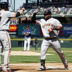 San Francisco Giants on-deck batter Aubrey Huff, left, congratulates Pablo Sandoval as Sandoval returns to the dugout after hitting a two-run home run against the Colorado Rockies in the first inning of a baseball game in Denver on Monday, April 9, 2012.