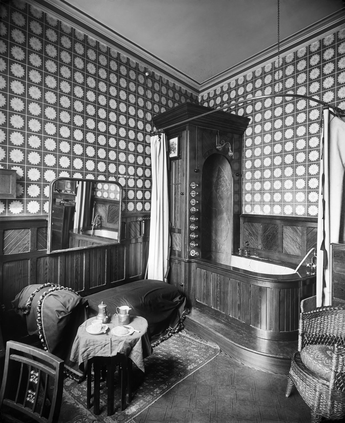 An archival photo of a Victorian bathroom featuring a wicker chair, rug, wood cabinetry around the bathtub, and wainscoting.