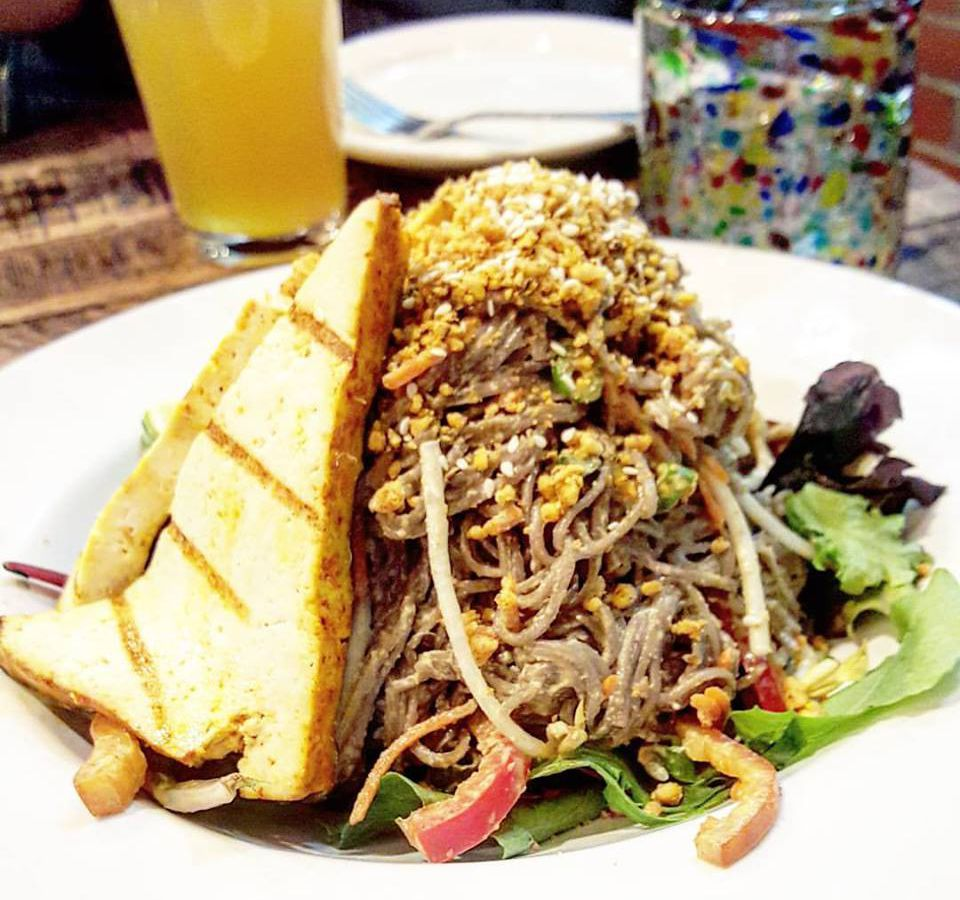 A giant mountain of skinny beige noodles sit on a pile of greens. A large triangle of grilled tofu sits along the side of the noodle pile.