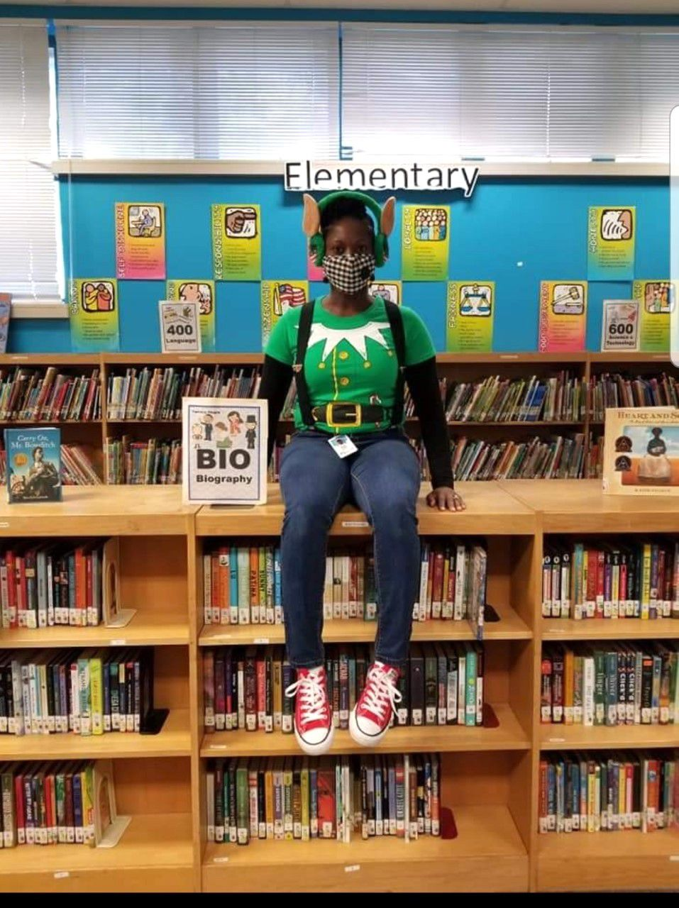Maude F. Graham sits on top of a shelf in her school's library dressed as the holiday character Elf on the Shelf.