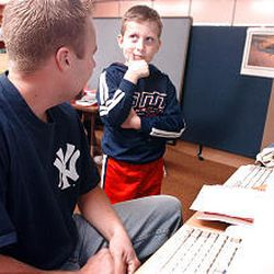 Logan Brown ponders what he wants to say in his e-mail to his grandma as counselor Chris Bertoldi waits to type it at the Panther Den at Hill Field Elementary.