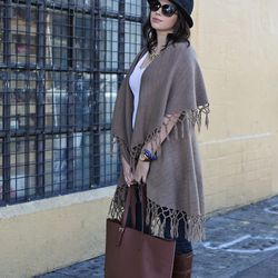 Caroline expertly combined a poncho and hat. She looks chic, not like she's heading to a costume party. Her shirt and bag are from Everlane, her jeans are Madewell, the boots are Tory Burch, the poncho is from a shop in LA, her hat is H&M, and her necklac