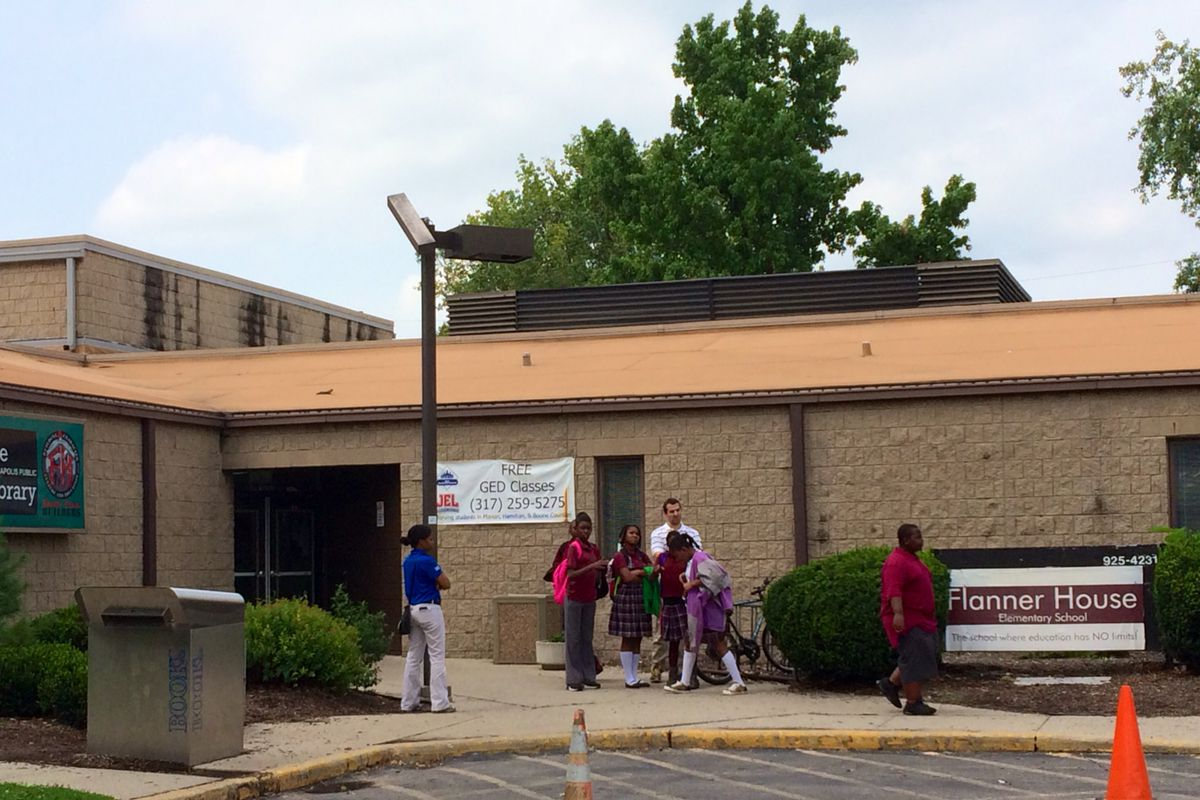 Students stand outside of Flanner House Elementary charter school in August as their parents learn about the schools impending closure in a private meeting. The school, which closed Sept. 11, was accused of cheating on the state ISTEP exam by the mayor's office and the state.