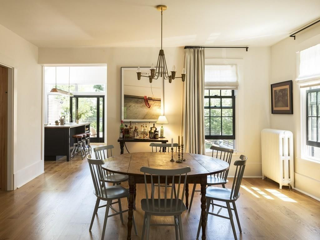 A squarish dining room with a table and chairs.