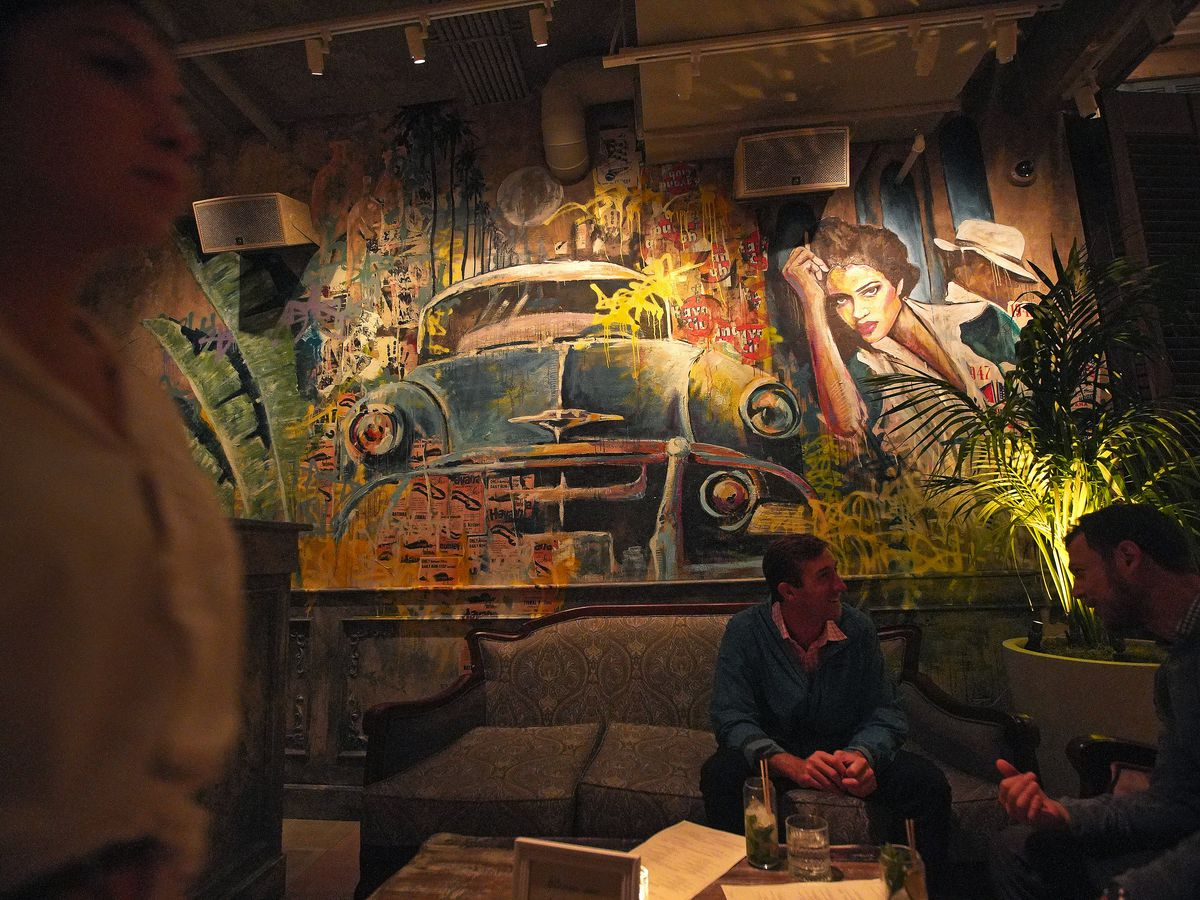A cozy restaurant with a mural on the wall.
