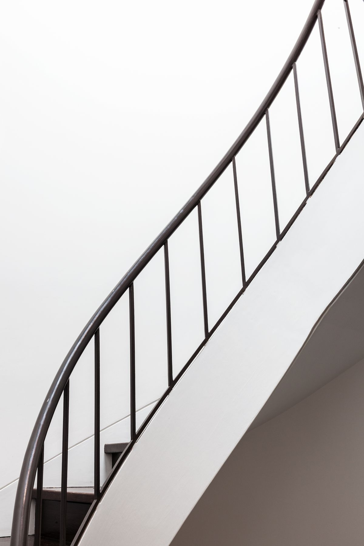A curving staircase with a metal handrail and spindles stretches up to a skylight.