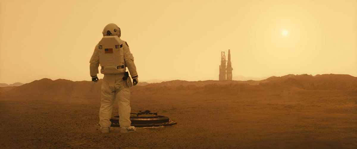 """A man in a spacesuit looks across a barren plain toward a rocket on a launch pad in the movie """"Ad Astra."""""""
