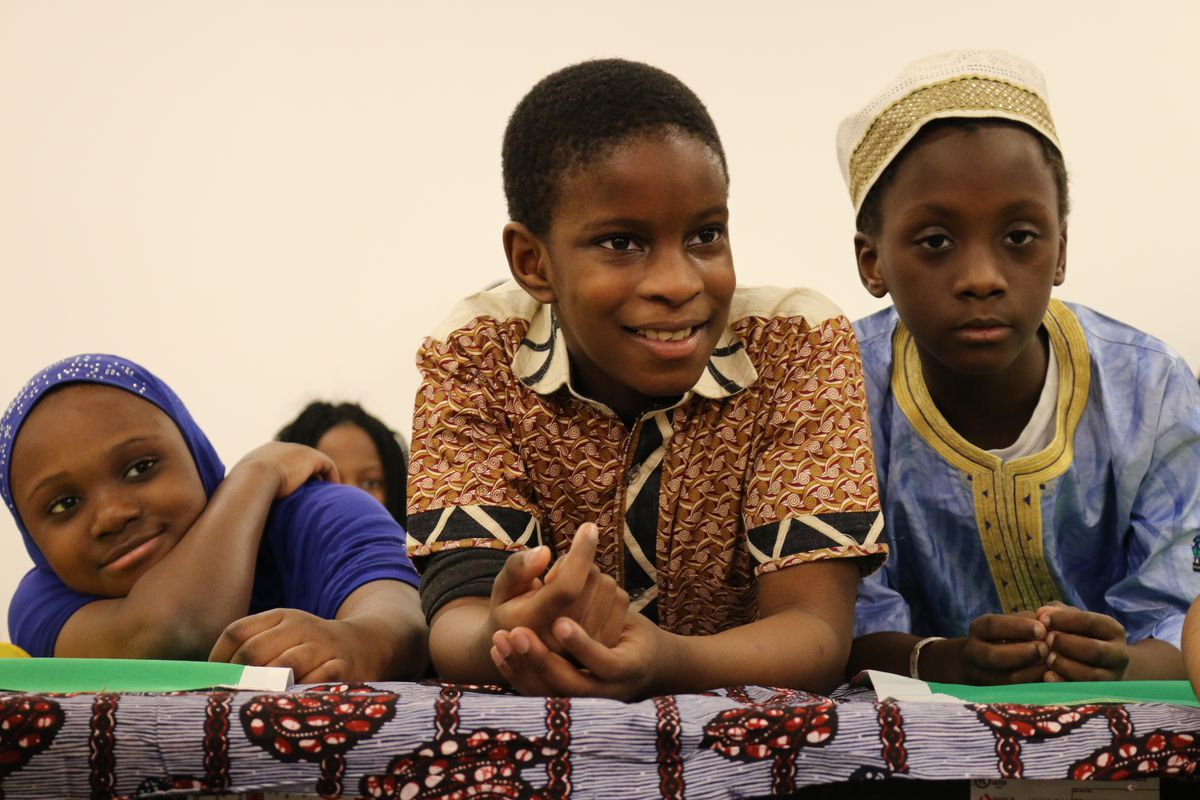 Students listen to a Nigerian folktale before sharing a Senegalese meal at a recent Celebrate Africa event.